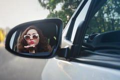 Отражение жизнерадостной красивой девушки в бортовом зеркале автомобиля Стоковая Фотография
