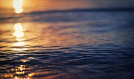 Отражение захода солнца в воде озера с волнами стоковые фотографии rf