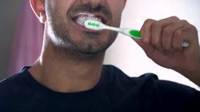 Отражение молодого человека чистя его зубы щеткой в bathroom Изображение конца-вверх человека чистя зубы щеткой в квартире акции видеоматериалы