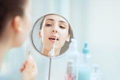 Отражение молодой женщины брюнет кладя на уборную lipgloss Стоковые Фотографии RF