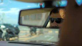 Отражение мужской стороны в солнечных очках в зеркале заднего вида в moving автомобиле, движение сток-видео