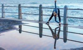 Отражение на влажной дороге женщины делая простирания Стоковое Изображение