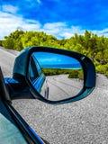 Отражение на зеркале автомобиля пока управляющ Стоковое Фото