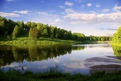 Отражение неба в сини спокойного озера Лес, загоренный по солнцу, на противоположном банке E стоковые фото