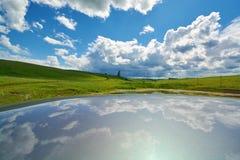Отражение неба с облаками на крыше автомобиля Стоковое фото RF