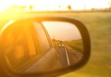 Отражение солнечной дороги и захода солнца на mirrow стороны автомобиля Стоковая Фотография