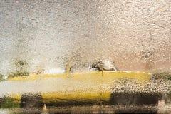 Отражение старого желтого автомобиля на влажном асфальте во время дождя Стоковые Изображения
