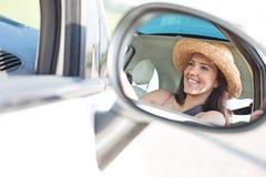 Отражение счастливой женщины в зеркале заднего вида автомобиля Стоковое Изображение