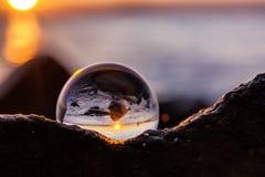 Отражение хрустального шара на seashore в свете восхода солнца Стоковые Фотографии RF