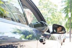 Отражение человека в зеркале стороны водителя автомобиля Стоковое фото RF