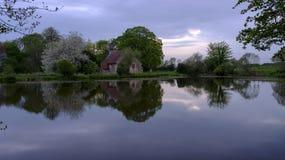 Отражения церков St Leonard в пруде Hartley Mauditt, южные спуски национальный парк, Великобритания стоковые фото