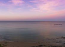Отраженный заход солнца над морем и пляжем Стоковое фото RF