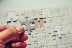 Отрегулируйте часть белых головоломок которые около упасть для того чтобы получить a Стоковая Фотография