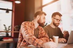 Отрежьте взгляд 2 битников изучая в кафе Одно из их работает на компьютере пока другое одно lookint на чем его Стоковое Изображение
