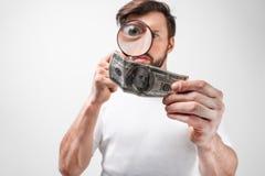 Отрежьте взгляд молодого человека который держит 100 долларовых банкнот и смотреть на ем через loupe Он хочет чтобы быть уверенны Стоковое Фото
