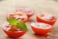 Отрежьте в половинных томатах вишни с лист базилика дальше Стоковые Фотографии RF