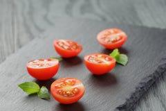 Отрежьте в половинных томатах вишни с лист базилика дальше Стоковые Изображения