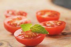 Отрежьте в половинных томатах вишни с лист базилика на деревянной таблице Стоковое Фото