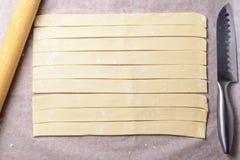 Отрежьте в прокладки теста на бумаге выпечки Стоковое Изображение RF