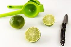 Отрежьте известки при juicer и нож изолированные на белизне Стоковая Фотография