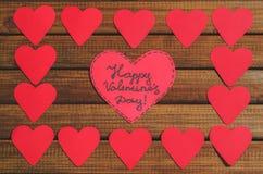 Отрежьте из красных бумажных сердец на деревянной предпосылке, поздравлении с днем ` s валентинки Стоковое Изображение