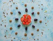 Отрежьте клубники на таблице среди разбросанных хлопьев на голубой предпосылке Стоковое фото RF