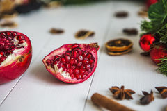 Отрежьте красное гранатовое дерево, циннамон, высушенные лимоны лежат на белом деревянном столе на предпосылке зеленых гирлянды и Стоковое Изображение