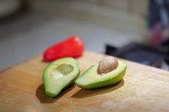 Отрежьте к половинному свежему органическому авокадоу с внутренностью типуна и красному болгарскому перцу на деревянной доске в к стоковое фото rf