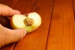 Отрежьте персик в man& x27; рука s Стоковая Фотография RF