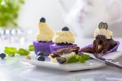 Отрежьте пирожное на белой плите с голубикой и фундуком в пурпурном обруче на мраморной столешнице стоковые фото