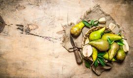 Отрежьте свежие груши на старой разделочной доске, с корзиной полной груш Стоковое Фото
