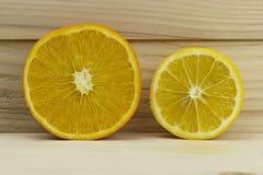 Отрежьте свежий сочный естественный лимон кислого апельсина на деревянной предпосылке Стоковые Фото
