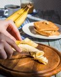 Отрежьте с ножом в части свежего, зрелого банана Стоковое Фото