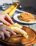 Отрежьте с ножом в части свежего, зрелого банана Стоковые Изображения