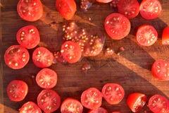Отрежьте томаты виноградины на деревянной разделочной доске Стоковое Изображение RF