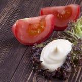 отрежьте томат пригорошня свирли майонеза на зеленых лист стоковые изображения rf