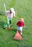 отрежьте траву сгребая сестер вверх Стоковая Фотография RF