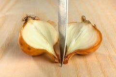 Отрежьте лук и нож на деревянной предпосылке Стоковые Фотографии RF