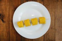 Отрежьте части кипеть corns на плите на деревянной предпосылке Стоковое Изображение