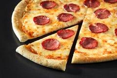 Отрежьте peperoni пиццы близкий поднимающий вверх на черной каменной предпосылке Стоковое Изображение
