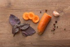 Отрезанная морковь, гвоздичное дерево чеснока, фиолетовая ветвь базилика и черное pe Стоковые Фотографии RF