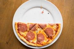 Отрезанная пицца салями на белой плите Стоковые Фотографии RF