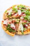 Отрезанная пицца с ветчиной Пармы ветчины, ракетой салата arugula и пармезаном на белом конце предпосылки вверх Стоковая Фотография