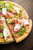 Отрезанная пицца с ветчиной Пармы ветчины, arugula & x28; rocket& x29 салата; и пармезан на темном деревянном конце предпосылки в Стоковая Фотография RF