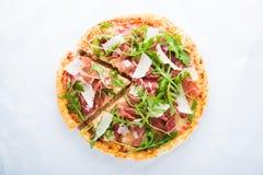 Отрезанная пицца с ветчиной Пармы ветчины, arugula & x28; rocket& x29 салата; и пармезан на белом взгляд сверху предпосылки Стоковая Фотография RF