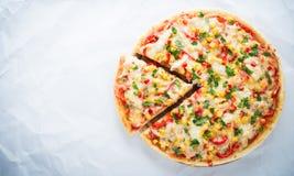 Отрезанная пицца с сыром моццареллы, цыпленком, сладостной мозолью, сладостным перцем и петрушкой на белом взгляд сверху предпосы Стоковая Фотография RF