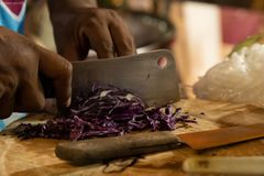 Отрезанная пурпурная капуста на деревянной доске с большим ножом стоковые изображения