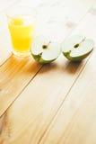 Отрезанное зеленое яблоко с стеклом сока Стоковая Фотография