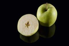 Отрезанное яблоко на черном зеркале Стоковые Фотографии RF