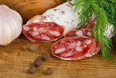 Отрезанное salame на разделочной доске, с укропом и перцем стоковое фото